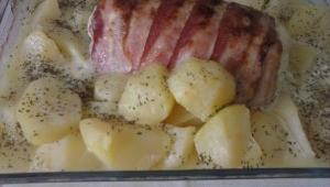 Rollo de carne con beicon, con guarnición de patatas y salsa de cebolla.